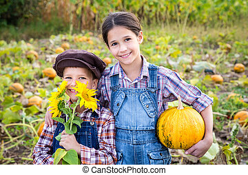 Two kids in vegetable garden - Two kids standing with...