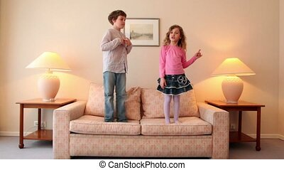 Two kids jump on sofa and then run away from room with lamps...