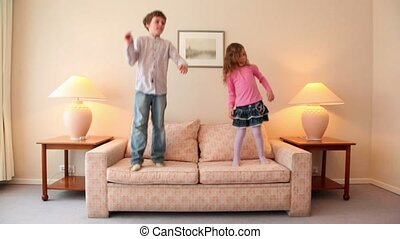 Two kids jump on sofa at room with lamps on each side - Two...