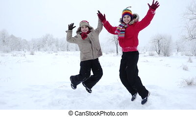 Two kids jumping together on winter landscape, slow motion