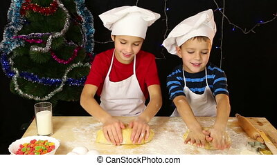 Two kids kneading the dough for christmas cookies