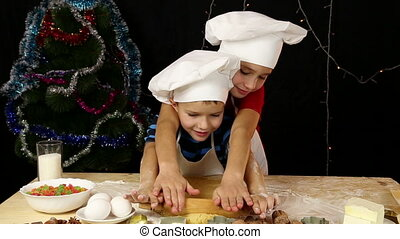 Two kids kneading the dough for xmas cookies together
