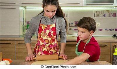 Two kids kneading the dough, making the pizza
