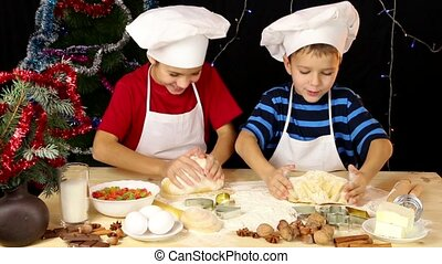 Two kids kneading the dough
