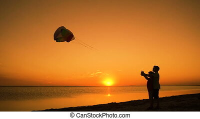 Two kids launching the rainbow kite together at sunset -...