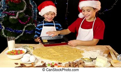 Two kids lay out the dough to baking tray