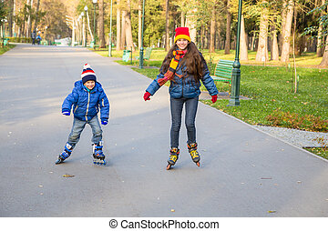 Two kids learning to ride in autumn park on rollerblades