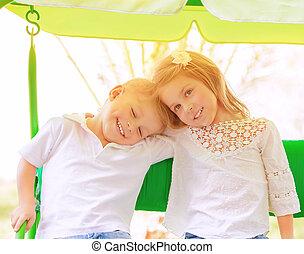 Two kids on swing
