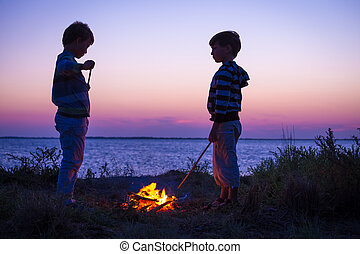 Two kids on the beach with campfire at sunset