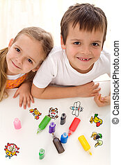 Two kids painting with lots of colors