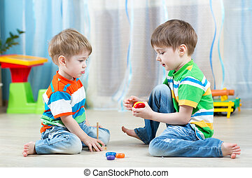 Two kids play with wooden toy sitting on the floor