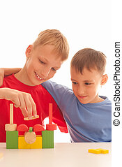 Two kids playin with brick-sat