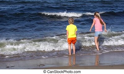 kids playing at the beach - two kids playing at the beach