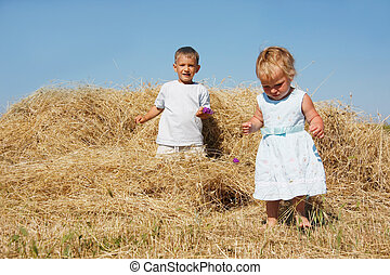 two kids playing in hay