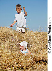 two kids playing in haystack