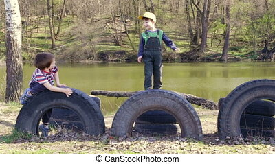 Two kids playing together jumping and climbing on old tires