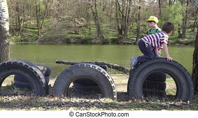 Two kids playing together, jumping and climbing on tires