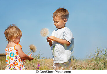two kids playing with big dandelions