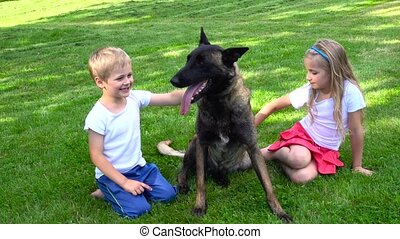two kids playing with dog outdoors