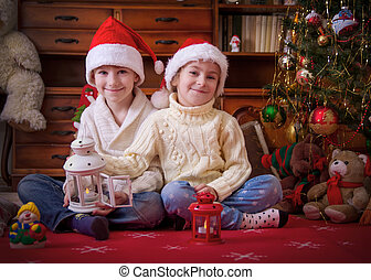 Two kids playing with lanterns under Christmas tree