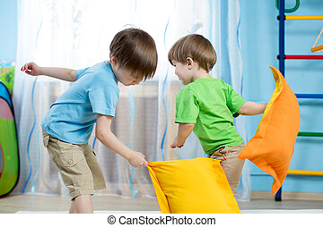 Two kids playing with pillows