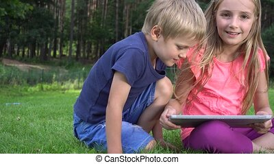 two kids playing with tablet outdoors on green grass