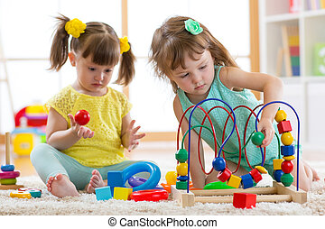 Two kids playing with wooden blocks in their room