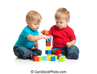 Two kids playing wooden blocks together building tower