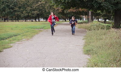 Two kids running on park - Two happy kids running on park,...