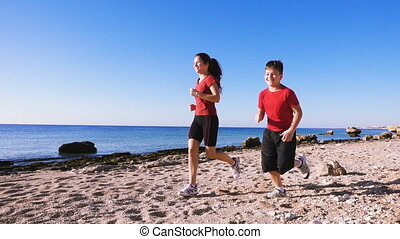 Two kids running together at morning exersises on coastline,...