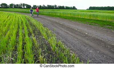 Two kids running together with bike on rural landscape