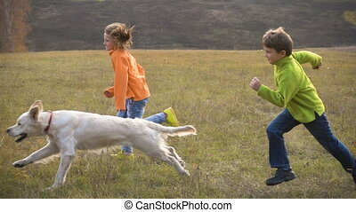 Two kids running with golden retriever at field - Two kids...
