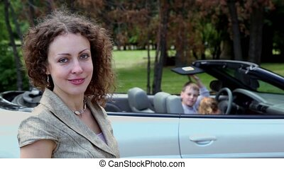 Two kids seat in cabriolet and their mother stand near closeup