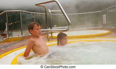 Two kids sit in pool with hot water, steam cover all around