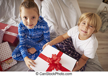 Two kids sitting on bed with Christmas present