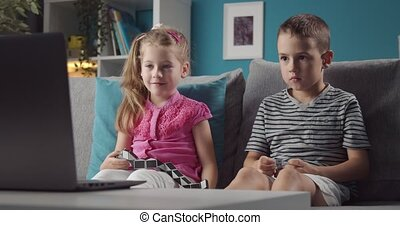 Two kids sitting on couch and watching cartoons on laptop