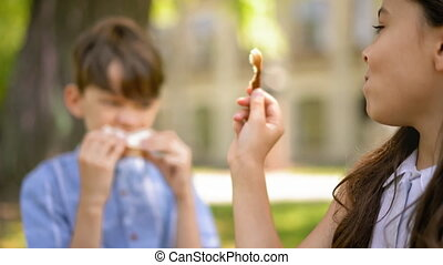 Two kids sitting outdoors the school eating sandwiches