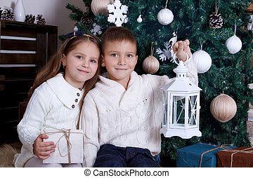 Two kids sitting with lanterns under Christmas tree