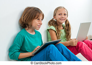 Two kids sitting with laptop and digital tablet.