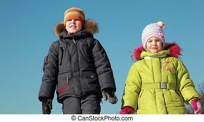 Two kids stand, look and tell something - Two kids in winter...