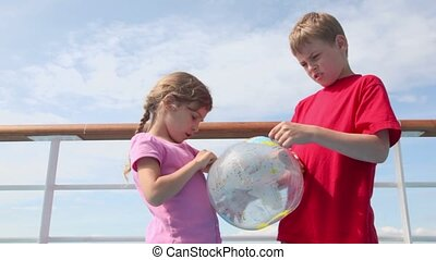 Two kids stand near railing and hold inflated ball