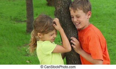 Two kids brother and little sister stand near tree and smile, girl scratches her head