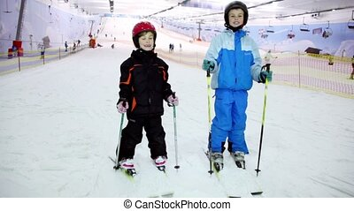 Two kids stand on ski and raises poles at background of ropeway