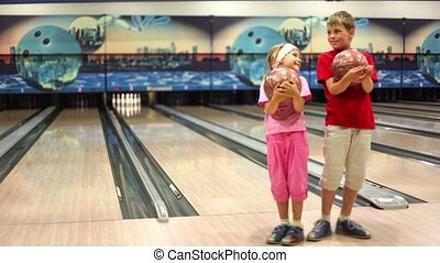 Two kids stand with balls in bowling club, then girl walks away and boy make throw