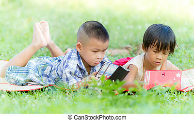 Two kids using touchscreen tablet PC on the grass