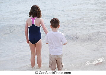 two kids wading into the ocean
