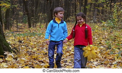 Two kids walking on autumn forest