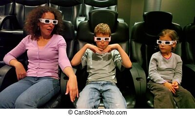 Two kids with their mother in 3d stereo glasses sit at cinema