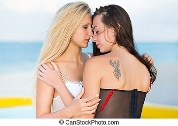 Two kissing women wearing sexy underwear