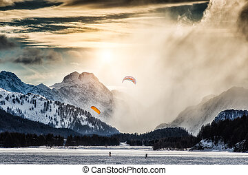 Two kite surfing on a frozen lake in the high mountains